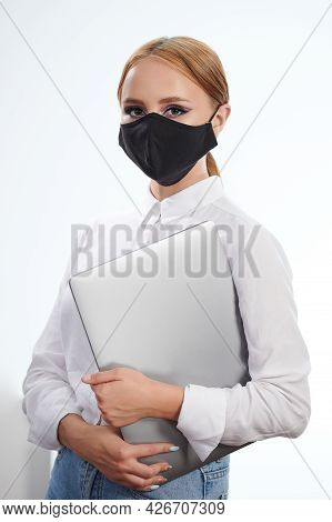 Young Woman Student In Mask Hold Laptop Isolated On White Studio Background