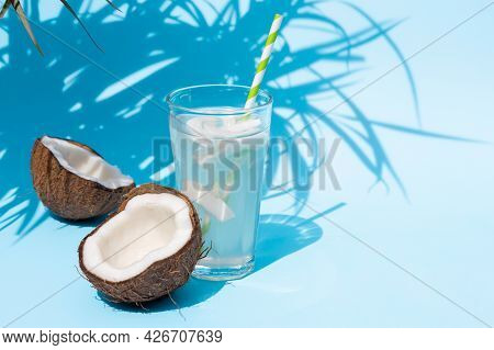 A Glass Of Fresh Organic Coconut Water, Milk On A Blue Pastel Background And A Ripe Half Of A Coconu