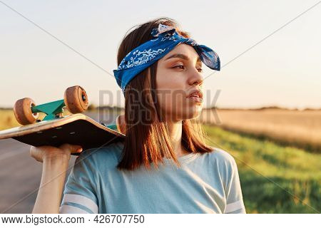 Pretty Dark Haired Female Wearing T Shirt And Hair Band Holding Skateboard On Her Shoulder And Looki