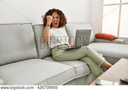 Middle age hispanic woman working using computer laptop at home annoyed and frustrated shouting with anger, yelling crazy with anger and hand raised
