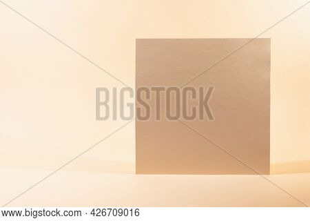 Gold Paper sheet or blank card on beige background. Creative background with empty sheet of paper with copy space.