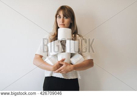 Woman with a pile of toilet tissue rolls