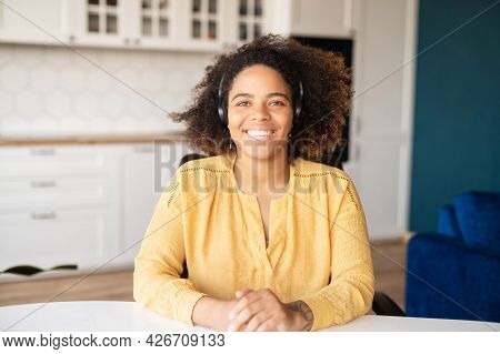 Headshot Of Friendly And Smiling African-american Woman Wearing Headset Sitting Indoor At The Home O