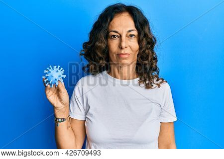 Middle age hispanic woman holding virus toy thinking attitude and sober expression looking self confident