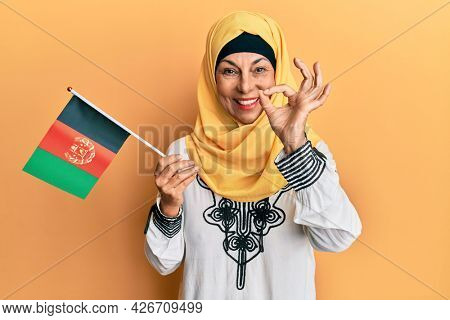 Middle age hispanic woman holding afghanistan flag doing ok sign with fingers, smiling friendly gesturing excellent symbol