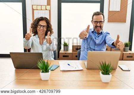 Middle age hispanic woman and man sitting with laptop at the office approving doing positive gesture with hand, thumbs up smiling and happy for success. winner gesture.