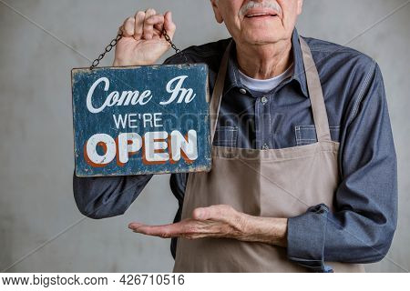 Senior man holding shop sign plate, come in we're open