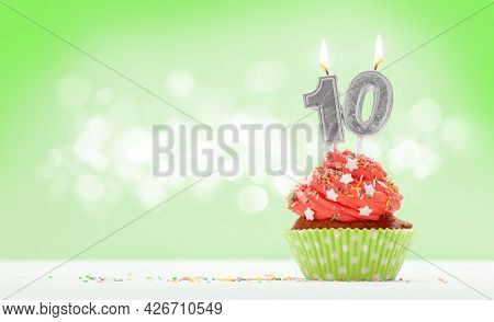 Birthday cupcake with number ten burning candle over green background with copy space for your greetings