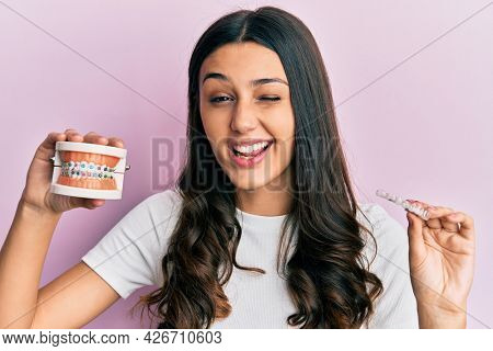 Young hispanic woman holding invisible aligner orthodontic and braces winking looking at the camera with sexy expression, cheerful and happy face.