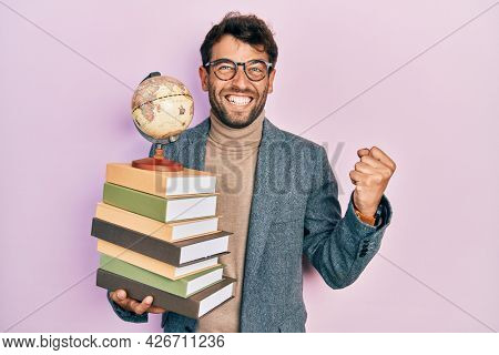 Handsome man with beard geography teacher screaming proud, celebrating victory and success very excited with raised arms