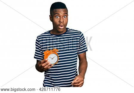 Young african american man holding alarm clock scared and amazed with open mouth for surprise, disbelief face