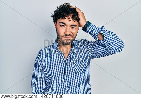 Young hispanic man wearing casual clothes confuse and wonder about question. uncertain with doubt, thinking with hand on head. pensive concept.