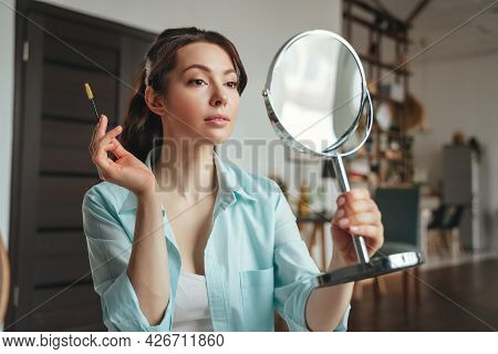Young Pretty Woman Does Makeup At Home While Looking In The Mirror