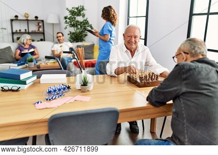 Two retired man smiling happy playing chess at nurse home.