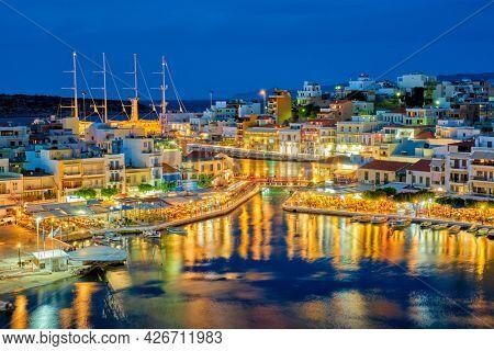 Beautiful Agios Nikolaos town on lake Voulismeni at night. Lasithi region of Crete island, Greece