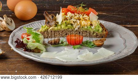 A Hearty Sandwich For A Balanced Diet. Rye Bread With Scrambled Eggs, Avocado, Salmon And Parmesan,