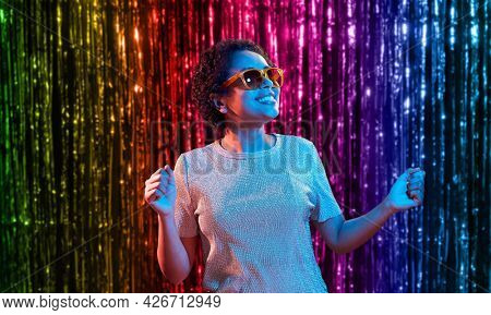 lgbt, clubbing and nightlife concept - smiling young african american woman in sunglasses dancing in ultraviolet neon lights over foil fringe curtain in rainbow colors background