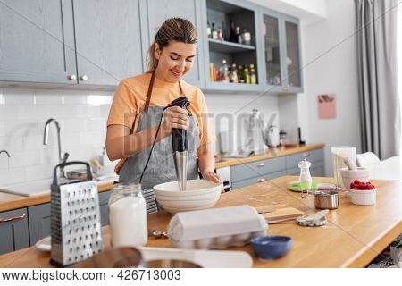 culinary, baking and people concept - happy smiling young woman cooking food on kitchen at home and using immersion blender