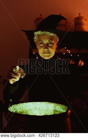 Old Witch Pouring Salt Into Her Magic Potion. Senior Person Dressed As A Witch Celebrating Halloween