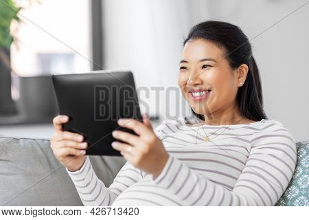 pregnancy, rest, people and expectation concept - happy smiling pregnant asian woman with tablet pc computer sitting on sofa at home