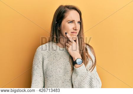 Young blonde woman wearing casual winter sweater thinking concentrated about doubt with finger on chin and looking up wondering