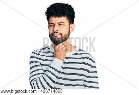 Young arab man with beard wearing casual striped sweater touching painful neck, sore throat for flu, clod and infection