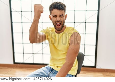 Arab young man getting vaccine showing arm with band aid annoyed and frustrated shouting with anger, yelling crazy with anger and hand raised