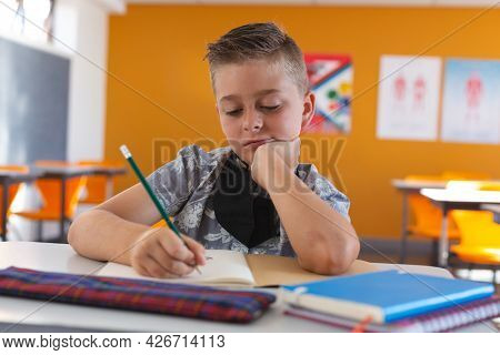 Caucasian schoolboy with face mask sitting in classroom concentrating and writing in schoolbook. childhood and education at elementary school during coronavirus covid19 pandemic.
