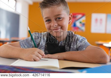 Portrait of smiling caucasian schoolboy with face mask sitting in classroom, writing in schoolbook. childhood and education at elementary school during coronavirus covid19 pandemic.