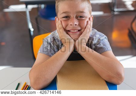 Happy caucasian schoolboy sitting at desk in classroom leaning on books and smiling. childhood and education at elementary school.