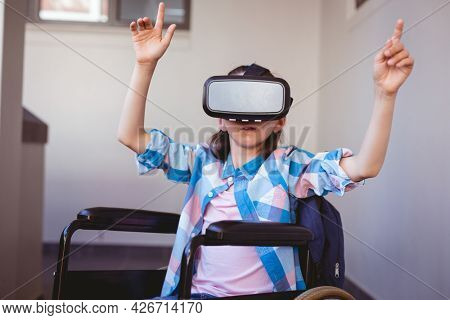 Disabled caucasian schoolgirl sitting in wheelchair wearing vr headset in school corridor. childhood, technology and education at elementary school.