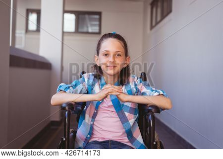 Portrait of smiling disabled caucasian schoolgirl sitting in wheelchair in school corridor. childhood and education at elementary school.