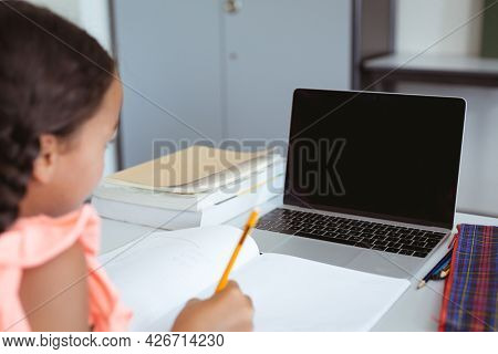 Mixed race schoolgirl sitting in classroom writing and using laptop, with copy space on screen. childhood, technology and education at elementary school.
