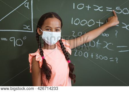 Portrait of mixed race schoolgirl in face mask standing in front of chalkboard pointing in classroom. childhood and education at elementary school during coronavirus covid19 pandemic.