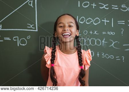 Portrait of laughing mixed race schoolgirl standing in front of chalkboard in classroom maths lesson. childhood and education at elementary school.