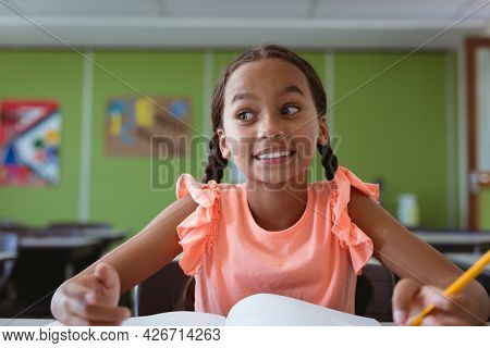 Portrait of smiling mixed race schoolgirl sitting at desk in classroom. childhood and education at elementary school.