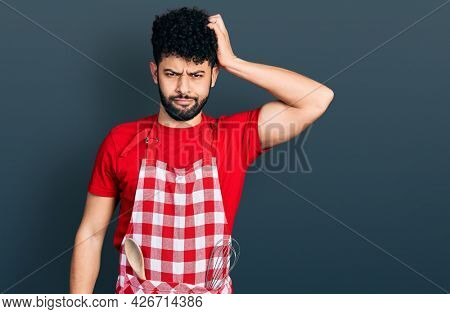 Young arab man with beard wearing cook apron confuse and wonder about question. uncertain with doubt, thinking with hand on head. pensive concept.