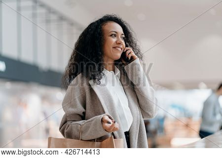 Young Woman With A Shopping Bag Talks On A Smartphone In A Shopping Center.