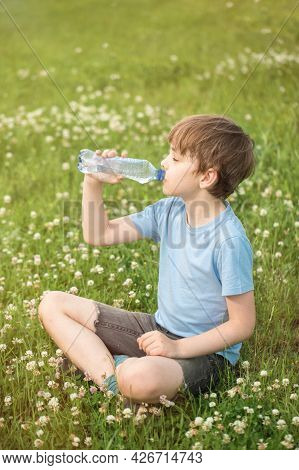 A Caucasian Boy Sits On The Grass Of A Lawn On A Hot Summer Day And Drinks Water From A Plastic Bott