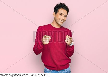 Young handsome man wearing casual clothes pointing fingers to camera with happy and funny face. good energy and vibes.