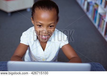 Smiling african american schoolgirl at desk in school library using laptop. childhood, technology and education at elementary school.