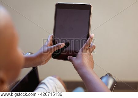 Disabled african american schoolboy sitting in wheelchair using tablet, copy space on screen. childhood, technology and education at elementary school. childhood and education at elementary school.