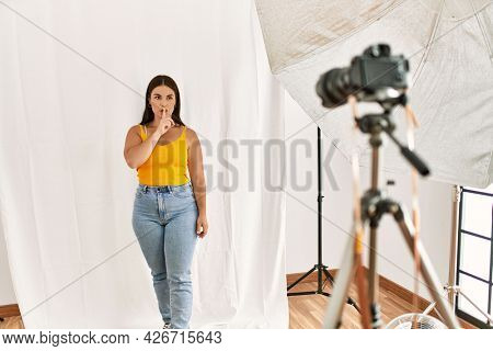 Young beautiful hispanic woman posing as model at photography studio asking to be quiet with finger on lips. silence and secret concept.