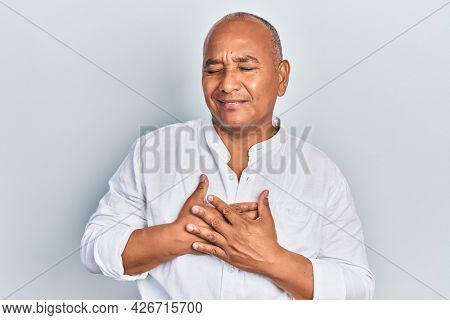 Middle age latin man wearing casual clothes smiling with hands on chest with closed eyes and grateful gesture on face. health concept.