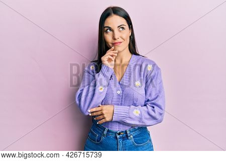 Young brunette woman wearing spring cardigan with flowers print thinking concentrated about doubt with finger on chin and looking up wondering