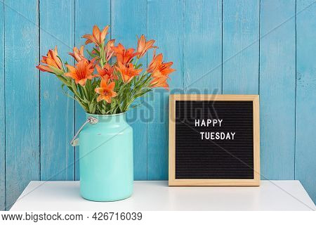 Happy Tuesday Words On Black Letter Board And Bouquet Of Orange Flowers On Table Against Blue Wooden