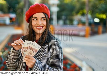 Young hispanic woman smiling happy counting russian ruble banknotes at the city.