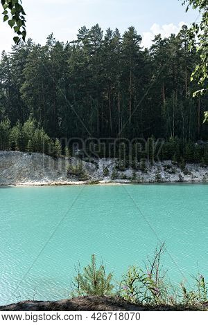 View Of The Blue Turquoise River Or Lake With Coniferous Wooded Banks, Beautiful Landscape With Brig