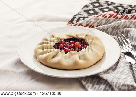 Homemade Sweet Galette With Elderberries And Cowberries On A Plate