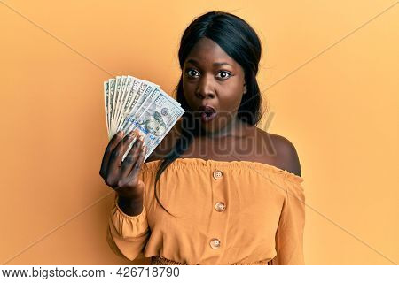 African young woman holding dollars scared and amazed with open mouth for surprise, disbelief face